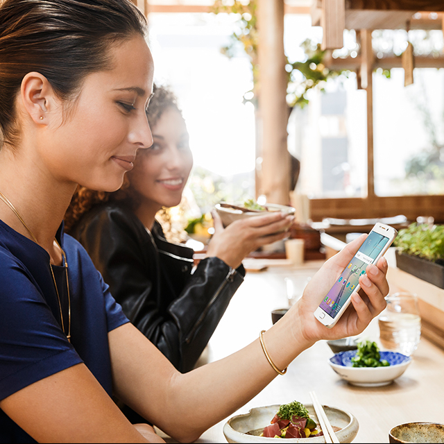 woman looking at her phone in a restaurant