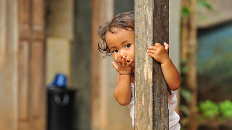 Young baby peering behind a wooden beam