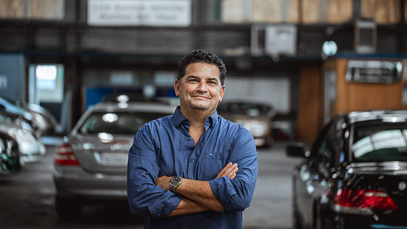 Man crossing his arms looking at the camera standing in a garage full of cars.