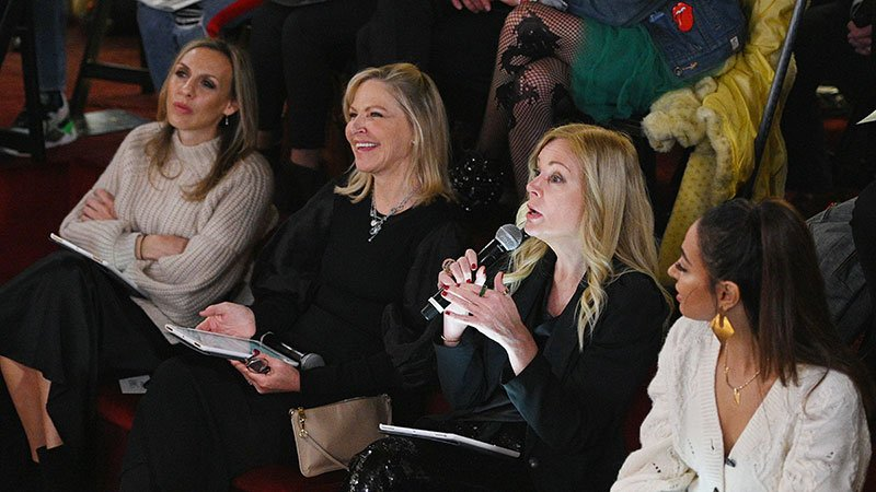 Four women sitting in a row judging a contest, one holding a microphone and speaking