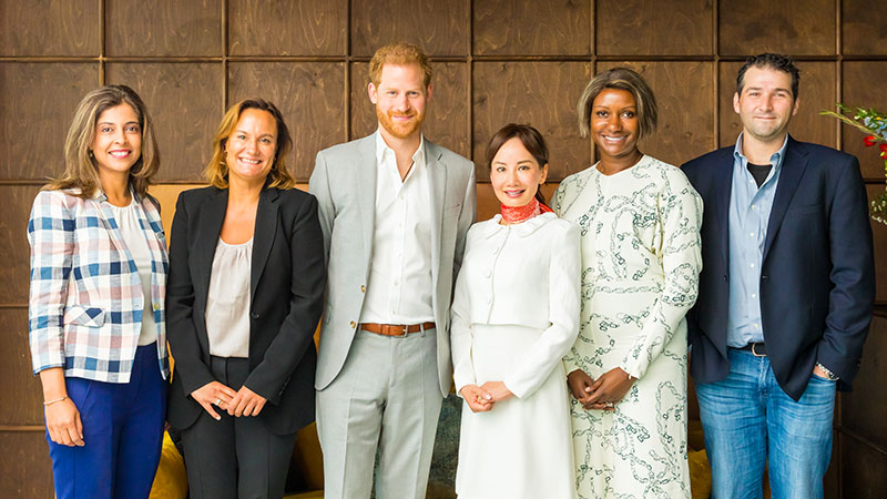 Group of panel speakers, including HRH The Duke of Sussex, smiling and standing against a brown wall