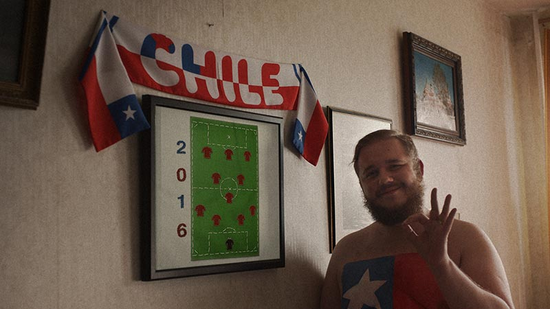 Football fan waving next to poster of 2016 football field layout with Chile banner above it.