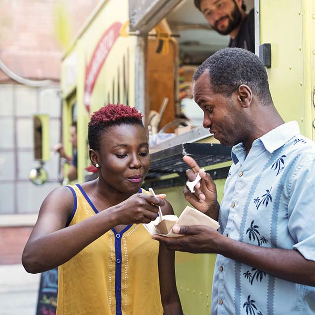 African-american couple enjoying their food from a food truck in city street