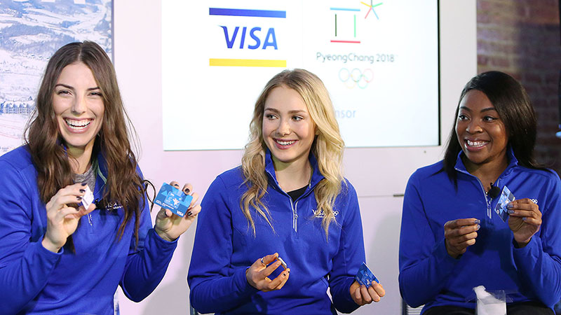 Olympians Hilary Knight, Maggie Voison, and Ngozi Onwumere hold up Visa payment wearables in front of a screen with the Visa and Olympics logos.