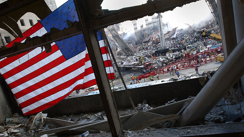 American Flag in a building that has collapsed with workers trying to rebuild in the background