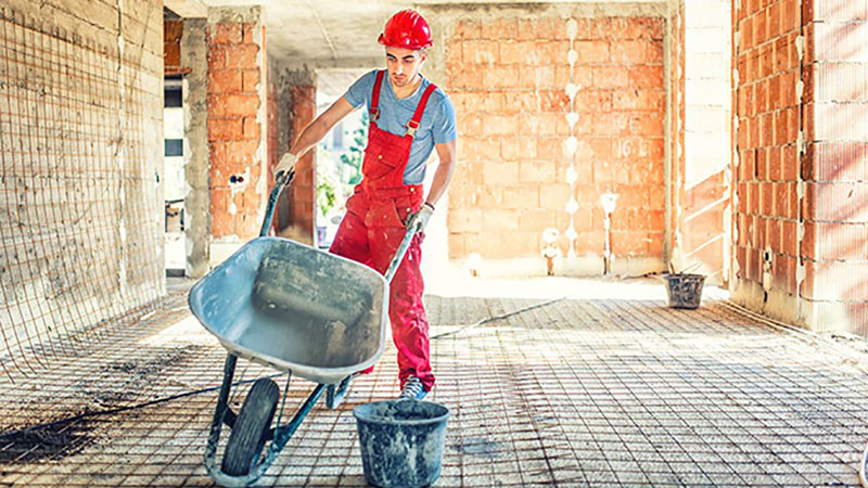 Man carrying a wheelbarrow in a red jumpsuit and hard hat, helping to construct a building