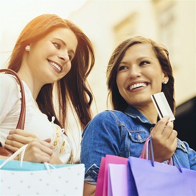 Two smiling women holding shopping bags.