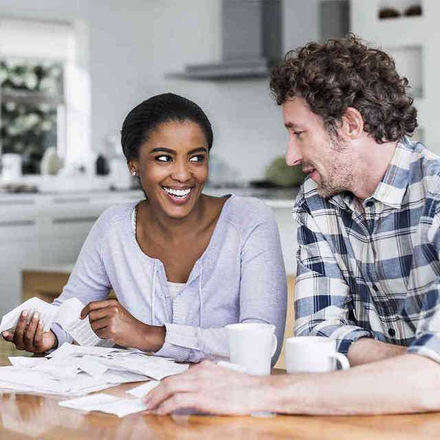 Man and woman looking at several paper bills while sitting at a table.