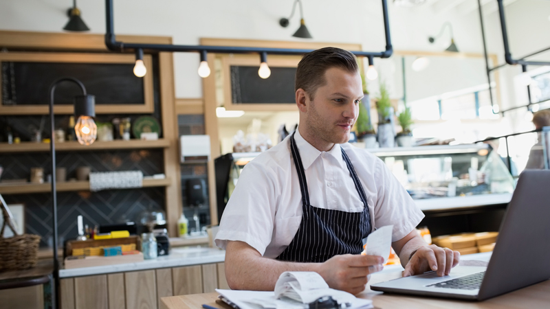 Man in an apron using a laptop