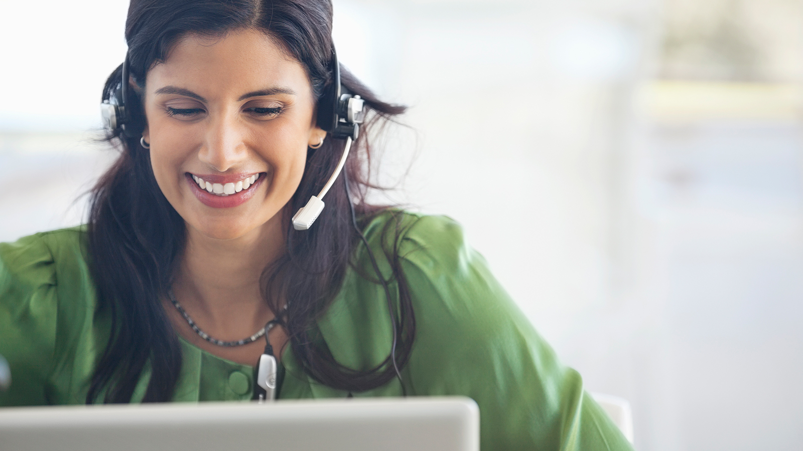 Woman on a laptop with a headset