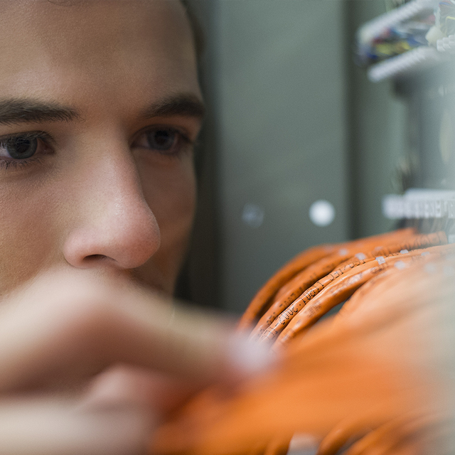 man inspecting ethernet cables in servers