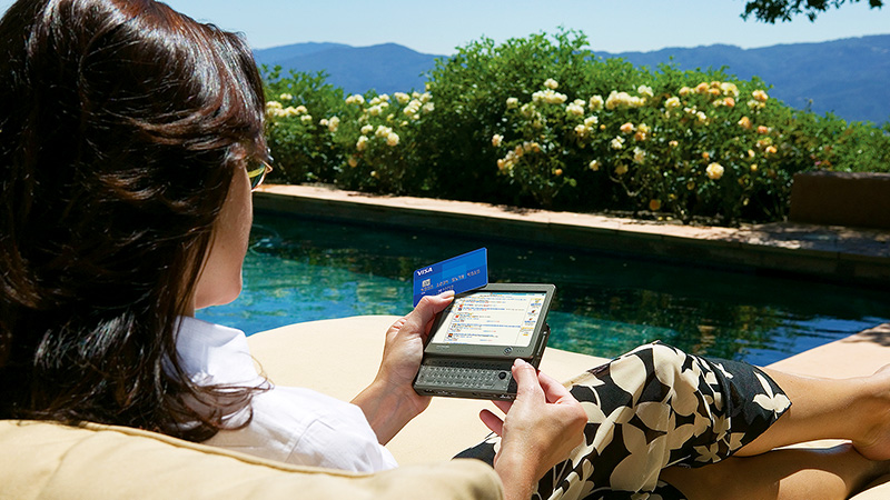 A woman lounging next to a pool while  holding a Visa card and a tablet in her hands.