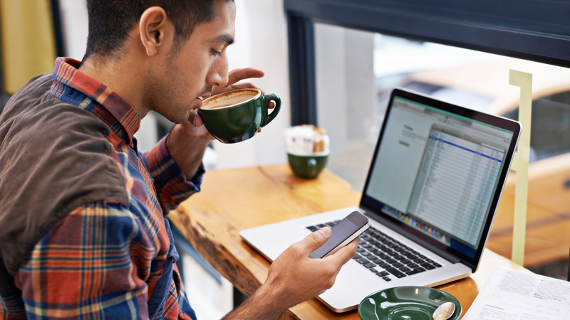 Man at a coffee shop sipping a cup of coffee in front of his laptop.