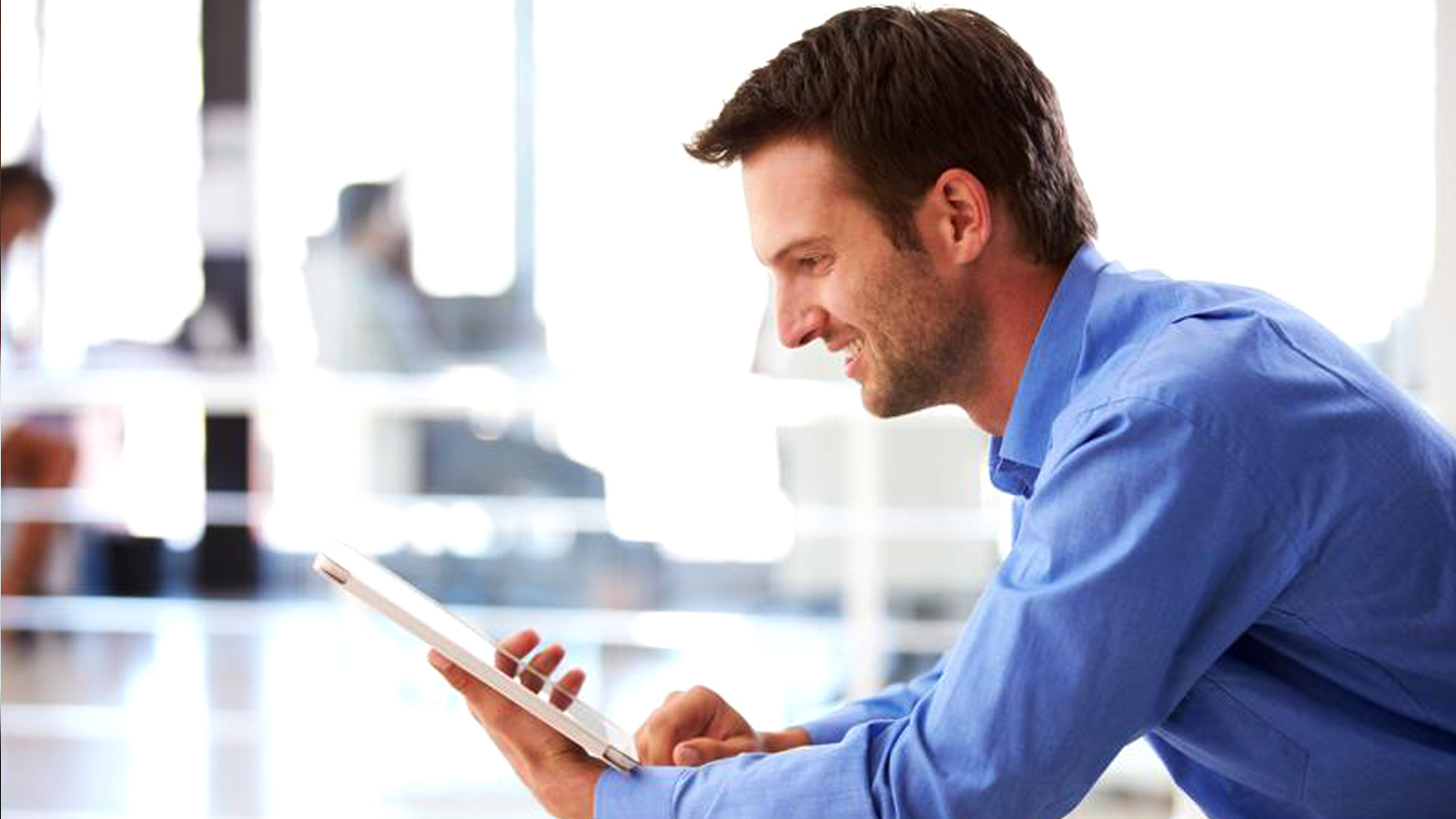 Man smiling at a tablet.