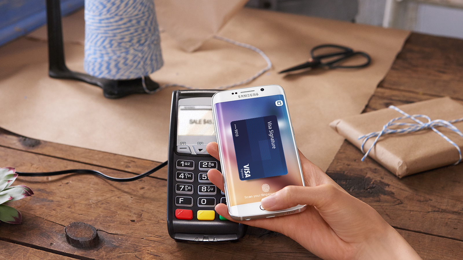 A hand holding a mobile phone over a POS device making a Samsung Pay payment.