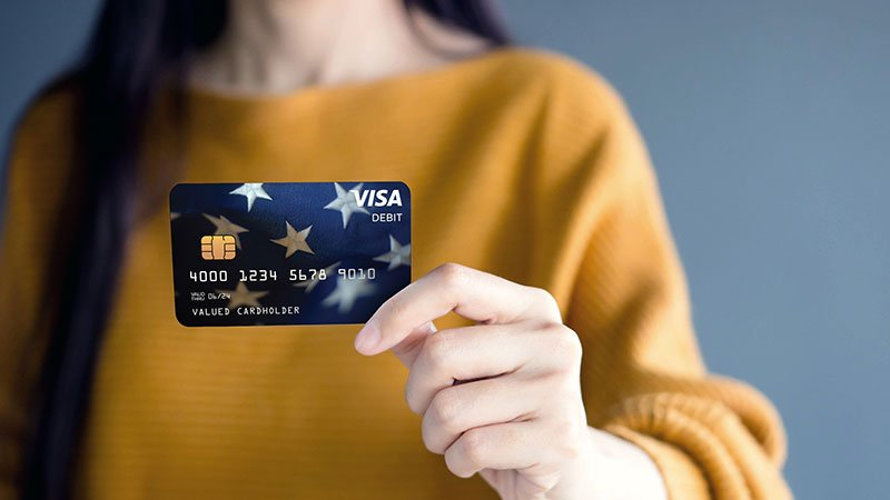 Women holds up a Visa prepaid debit card