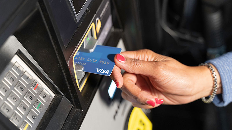 Woman's hand dipping a Visa chip-enabled card at a fuel pump