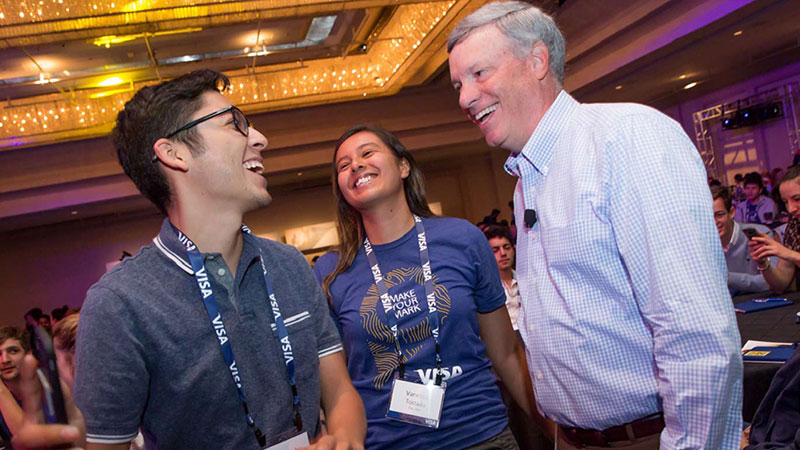 Visa CEO Al Kelly laughs while talking to two interns at the intern summit