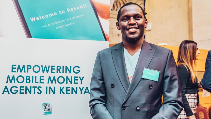 PesaKit founder and CEO Andrew Mutua stands in front of a sign for his company, which offers affordable e-float loans to mobile money agents in Kenya.
