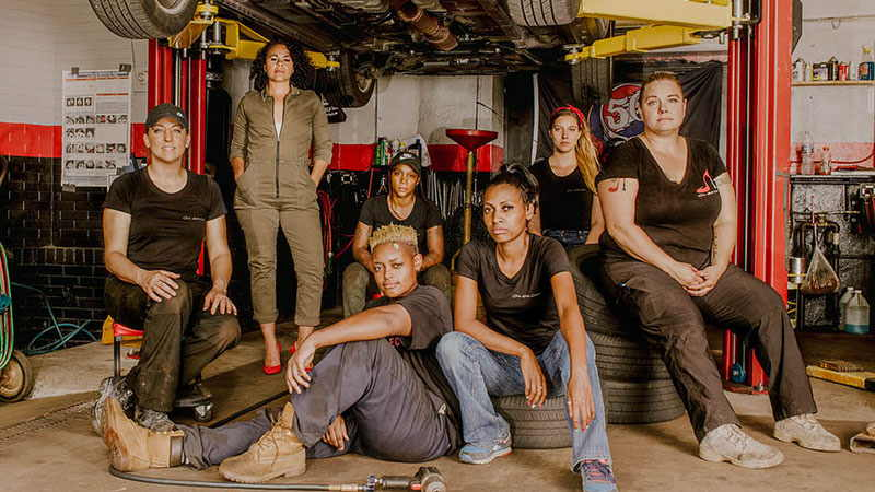 Seven women standing and sitting in a car shop wearing mechanics' clothing.
