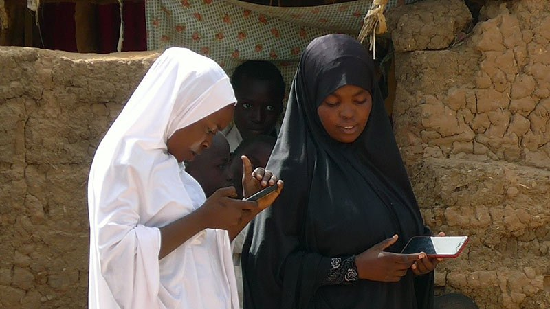 Two women holding phones are looking down at their hands in a marketplace.