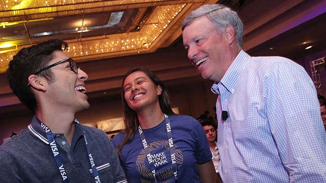 Two interns with Visa CEO, Al Kelly at Global Intern Summit