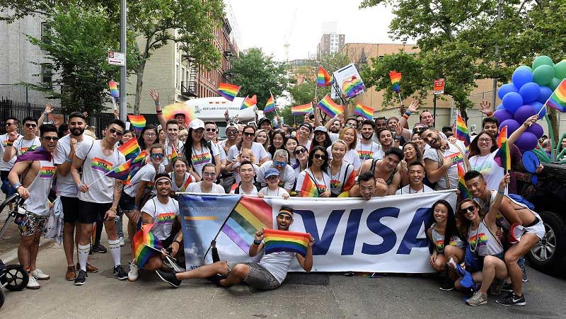 Large group of Visa group of employees standing in behind Visa banner at Pride Parade