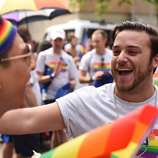 Men with rainbow flags and Visa shirts smiling and celebrating