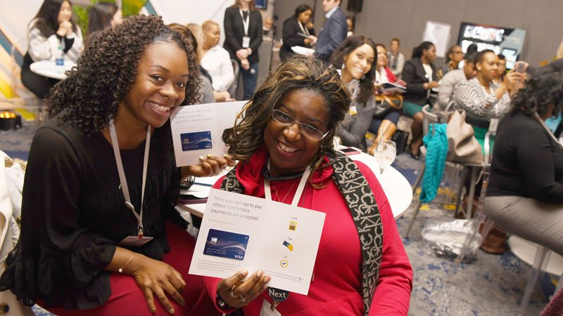 A pair of women smile for the camera at a Visa event