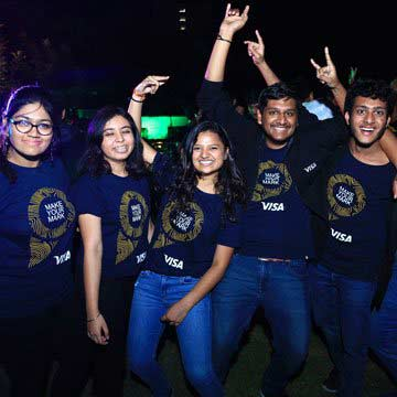 A co-ed group of interns in matching Visa t-shirts make silly poses for the camera at an event.