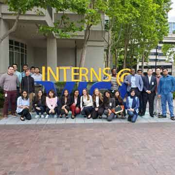 A large group of Visa interns pose in front of a interns sign at Visa's Foster City building.