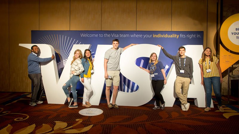 A co-ed group of smiling interns pose in front of a big Visa sign.