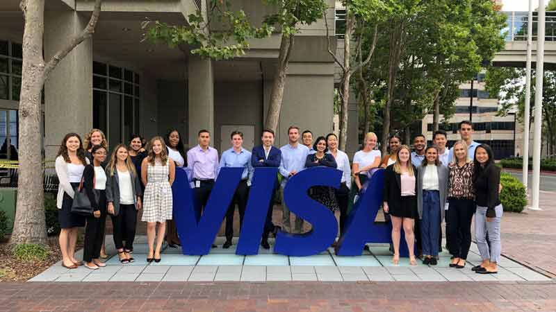 A co-ed group of well-dressed grads stand in front of a Visa sign at the company headquarters.