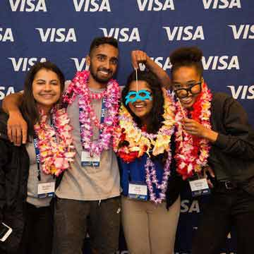 A group of interns wearing Hawaiian leis in front of a photo background with Visa written on it.