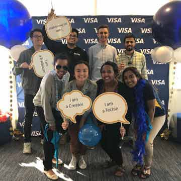 A group of interns pose in front of a Visa poster and balloons.