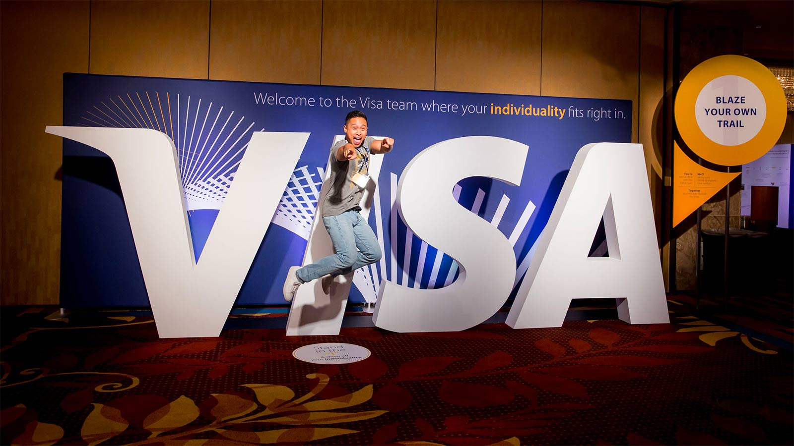 A male intern, in front of a Visa logo, jumps and points to the camera.