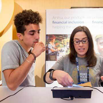 A pair of interns try out contactless payments with a card and reader at a Visa event.