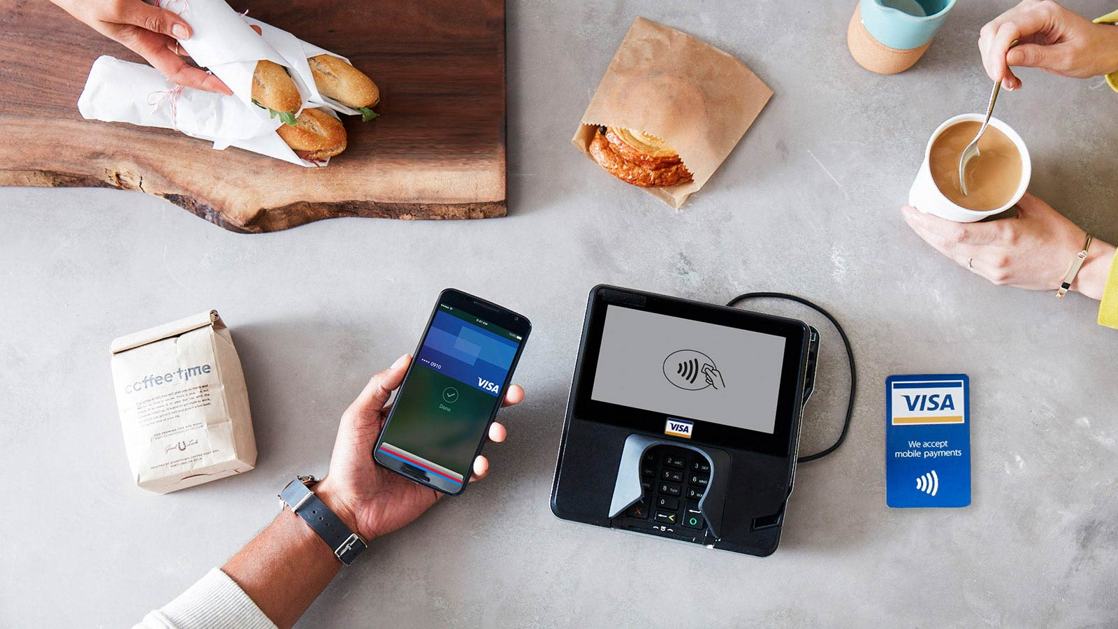 Paying for coffee shop items with Apple Pay at a contactless-enabled terminal.