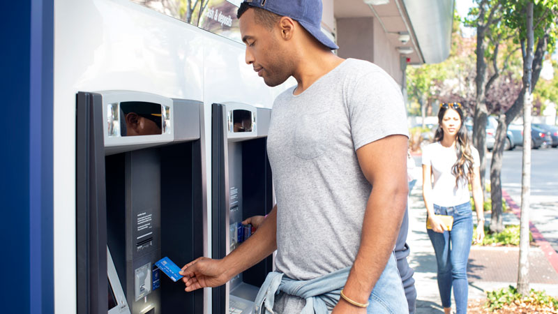 Man using his visa card near an ATM.
