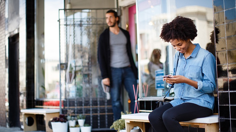 Woman sitting outside a store looking at her mobile phone and a man standing at the doorway.