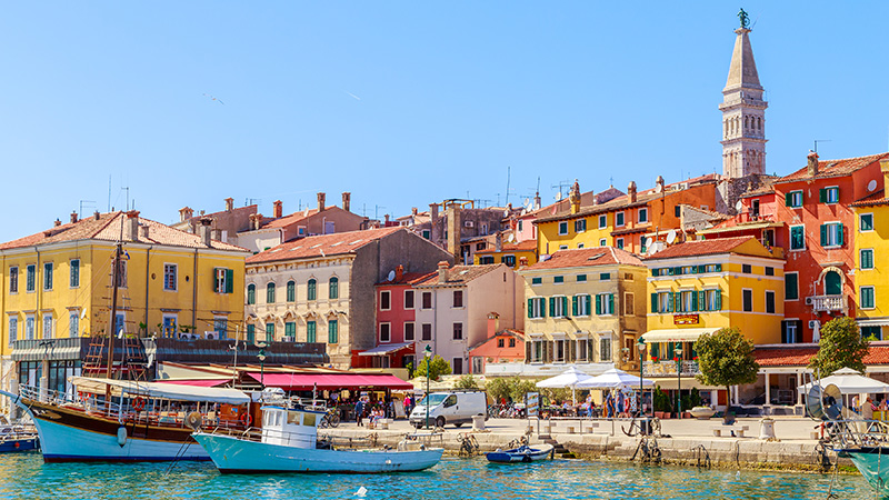 Image of a colorful town on the lake side with small boats.