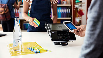 At a retailer, a young man purchases school supplies using his smart phone to make a contactless payment.
