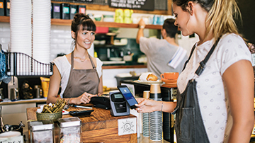 At a cafe, a young woman uses her smartphone to make a contactless payment on a terminal.