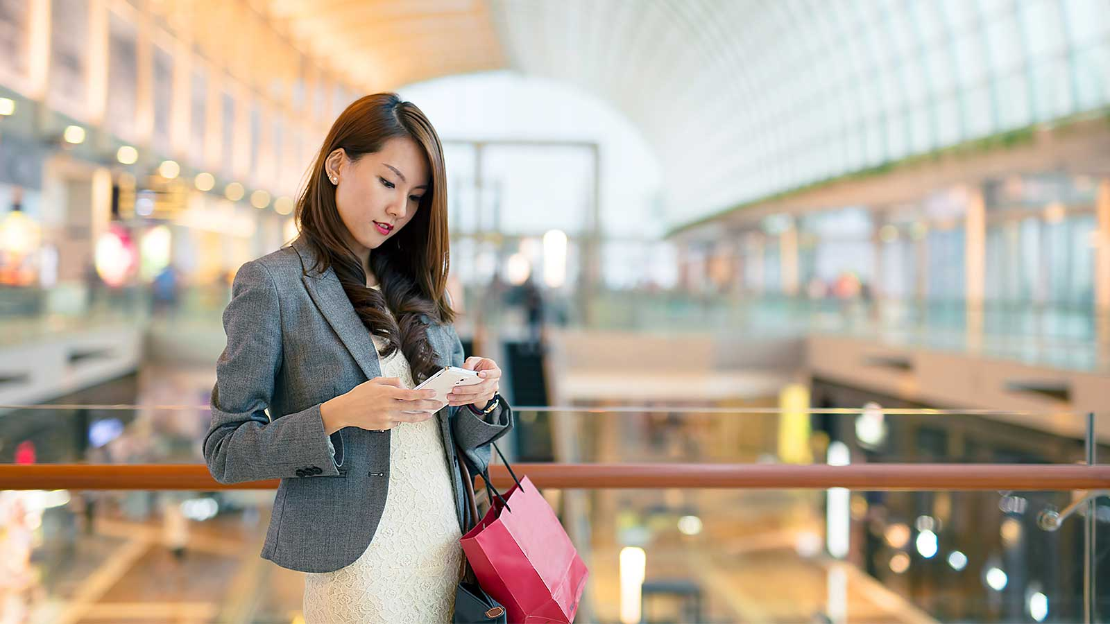 Woman with a shopping bag, looking at her mobile phone while inside a mall.