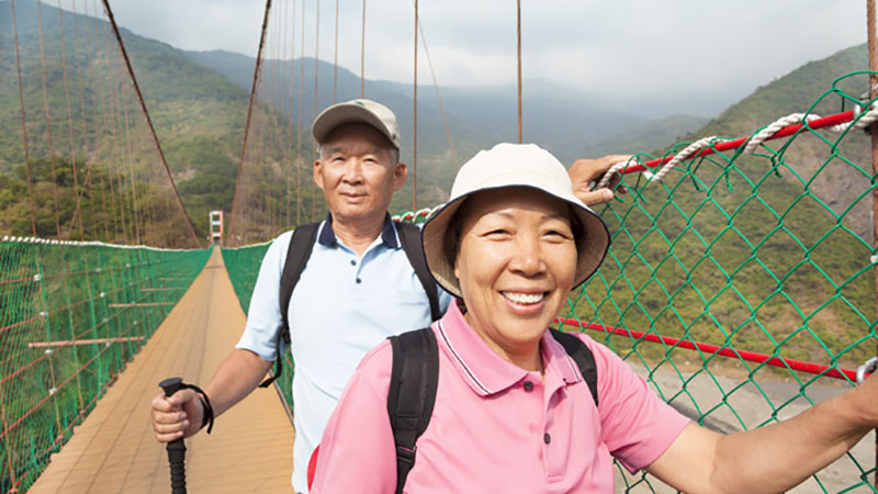 A man and woman standing on a hanging bridge.