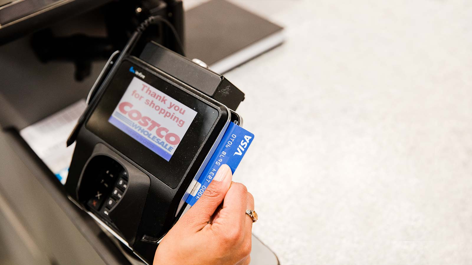 Costco member swiping a Visa card at checkout