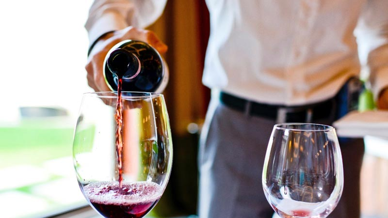 Man pouring wine in a glass at the Sonoma wine tasting event.