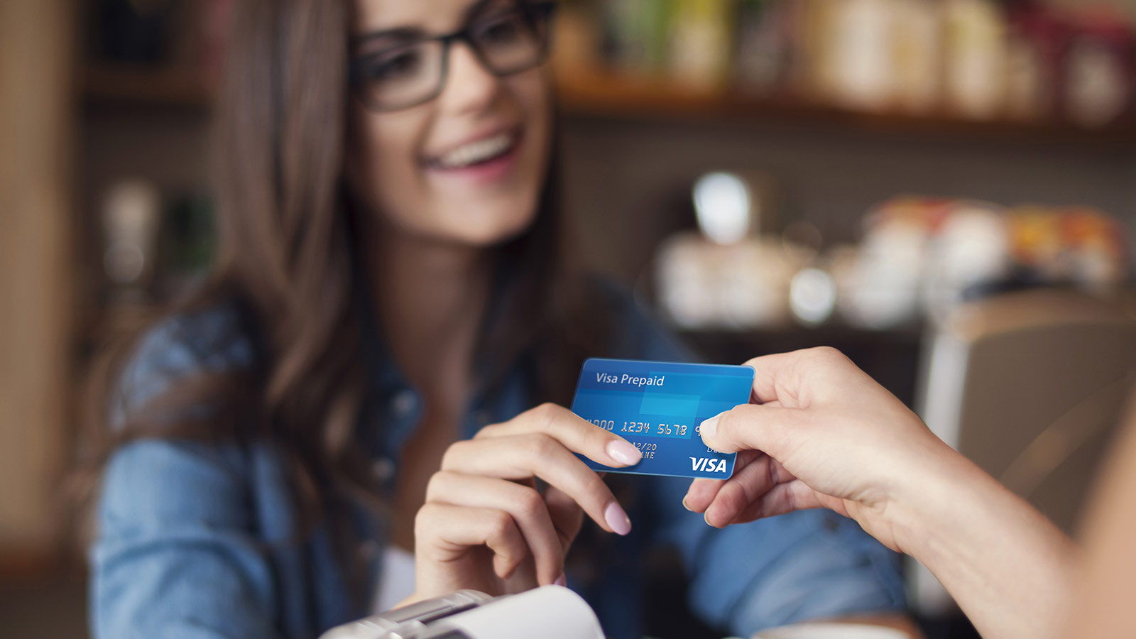 customer hands smiling cashier Visa prepaid card