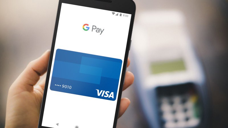 Hand holding a mobile phone with Google Pay Visa card shown on the screen.