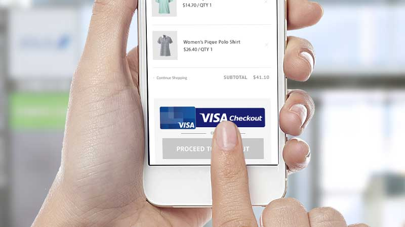 A hand holding a smart phone with the user's index finger clicking on a Visa Checkout button on a retailer website to complete the payment process.